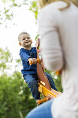 Child rides seesaw happily with his parent and smiles while in t