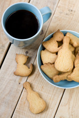 Sweet tasty cookies in the blue plate and cup of black coffee on