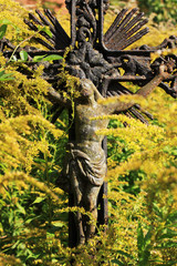 Jesus with yellow Flowers on the old village Cemetery