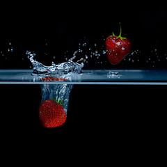 Strawberry falls into water. Strawberries in the air.