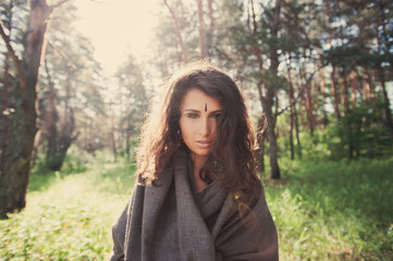 Portrait of a beautiful girl in a gray hooded in the forest