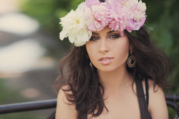 Portrait of a beautiful brunette girl in a wreath of peonies