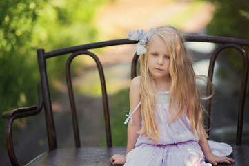 Beautiful blonde girl sitting on a vintage wooden bench