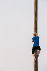 GOMEL, BELARUS - February 21, 2014 Young woman climbs on a wood
