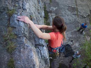 A young girl climbs the mountain.