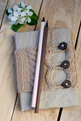 Old vintage notepad Knitted sweater in beige and pencils on the