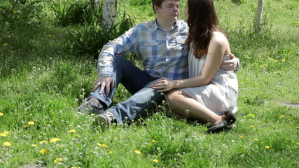 Loving couple sitting in the park on the grass in spring