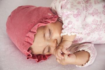 Bebita dormida con gorro rosa