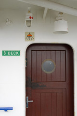 wooden door with a porthole on  ship