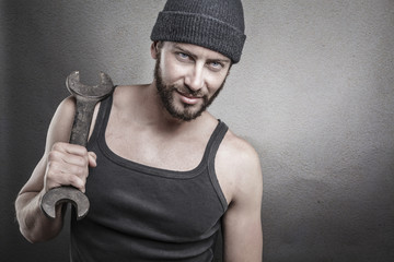 Handsome rough man holding a wrench over a textured grey backgro