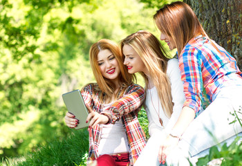 Three friends sitting in a park and making selfie with tablet