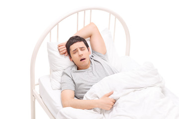 Young man sleeping in a bed and having nightmares