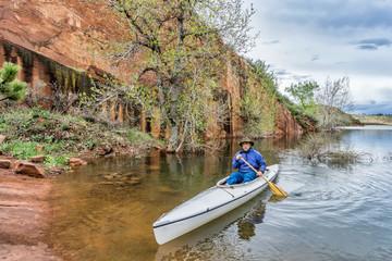 senio canoe paddler near sandstone cliff