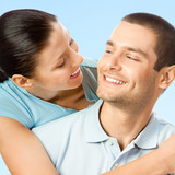 Young cheerful smiling amorous couple, on blue sky