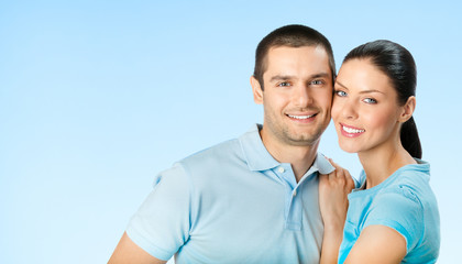 Cheerful smiling young couple, on blue sky