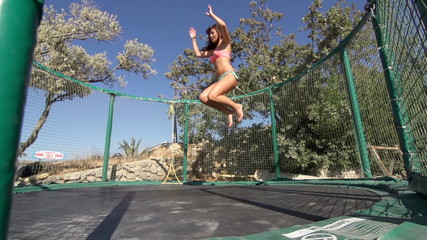Slow-Mo: Fit Young Woman Does A Somersault On The Trampoline