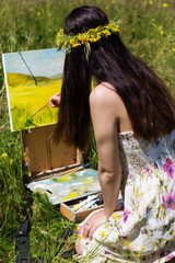 Pretty painter woman is create picture in a field