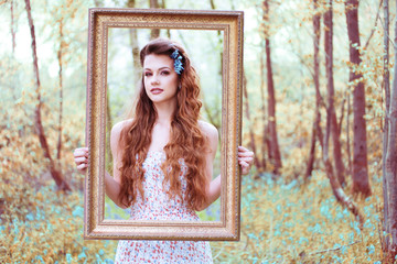 Ravishing woman looking through a portrait frame