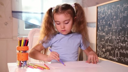 Little girl drawing with pencils sitting at the table