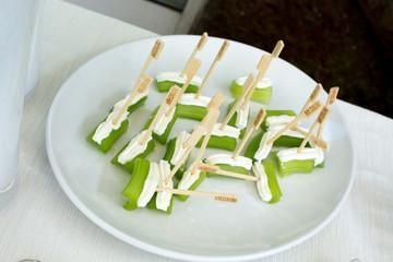 Sedano e formaggio spalmabile su piatto bianco
