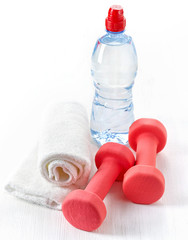 Fitness equipment dumbbells, towel and bottle of water
