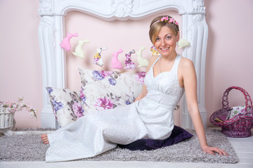 Young girl in a retro style wedding dress is sitting in a living