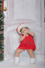 Child dressed as Santa is sitting on gifts