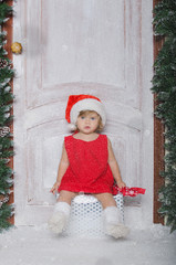 Girl in hat of Santa sitting on box with gifts