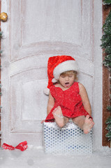 Child dressed as Santa is sitting on box and sings