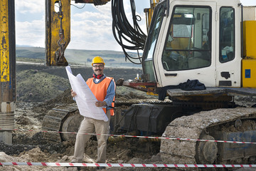 Mechanic engineer checking road plans in front of drilling pile