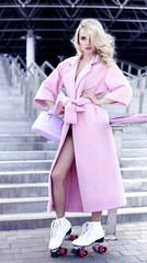 elegant blonde with  curling hair, poses on street in  coat