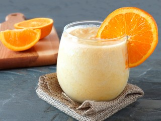 Healthy orange fruit smoothie in a stemless glass