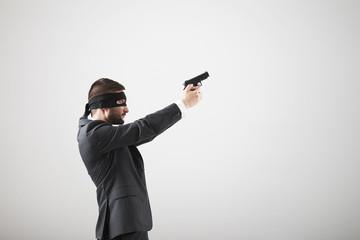 man in formal wear with gun