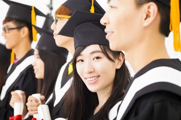 asian female college graduate at graduation with classmates