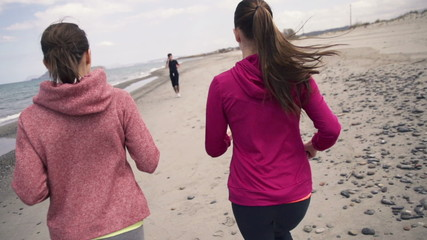 Young girlfriends jogging on the beach