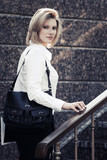 Young fashion business woman with handbag at office building