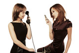 Two young fashion women with mobile and retro phone