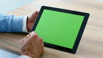 Closeup of man's hand sliding on tablet green screen