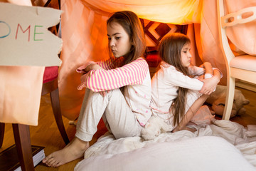 Two resentful sisters sitting on floor at bedroom back to back