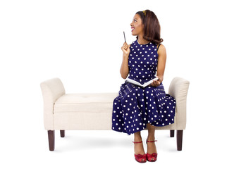 Black female author writing and on a chaise lounge
