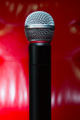 close up texture of microphone in music hall against red luxury