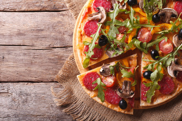 pizza with herbs, salami and vegetables horizontal top view