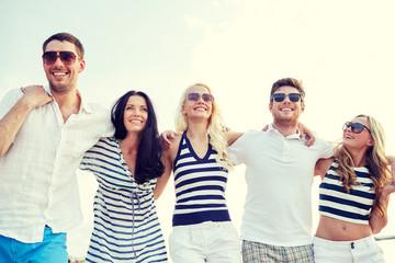 smiling friends in sunglasses walking on beach