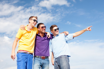 smiling friends in sunglasses pointing finger