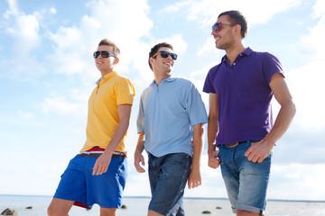smiling friends in sunglasses walking along beach