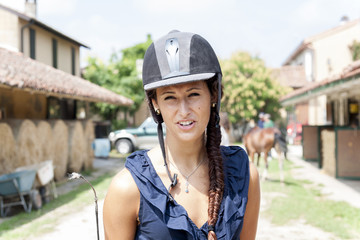 portrait of young horsewoman with helmet and whip