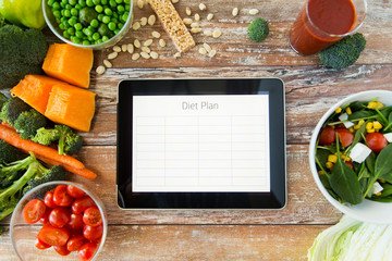 close up of diet plan on tablet pc and vegetables