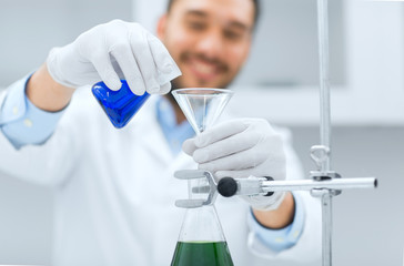 close up of scientist with test tubes and funnel