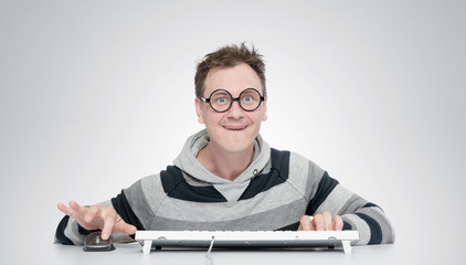 Funny man in glasses with a keyboard in front of computer