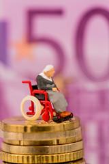Frau im Rollstuhl auf Geldstapel